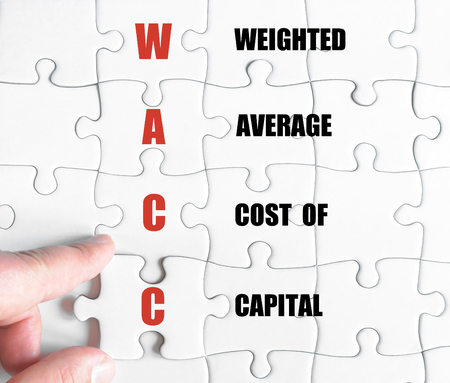 weighted: Hand of a business man completing the puzzle with the last missing piece.Concept image of Business Acronym WACC as Weighted Average Cost Of Capital Stock Photo