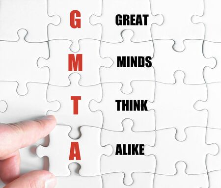 alike: Hand of a business man completing the puzzle with the last missing piece.Concept image of Business Acronym GMTA as Great Minds Think Alike