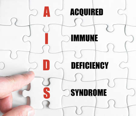 acquired: Hand of a business man completing the puzzle with the last missing piece.Concept image of Business Acronym AIDS as Acquired Immune Deficiency Syndrome Stock Photo