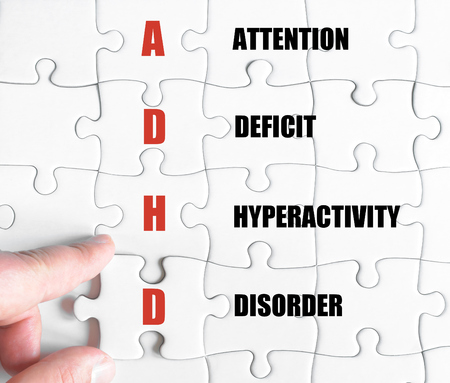 hyperactivity: Hand of a business man completing the puzzle with the last missing piece.Concept image of Business Acronym ADHD as Attention Deficit Hyperactivity Disorder
