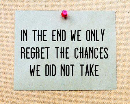 regret: In The End We Only Regret The Chances We Did Not Take written on paper note pinned with red thumbtack on wooden board. Motivation conceptual Image