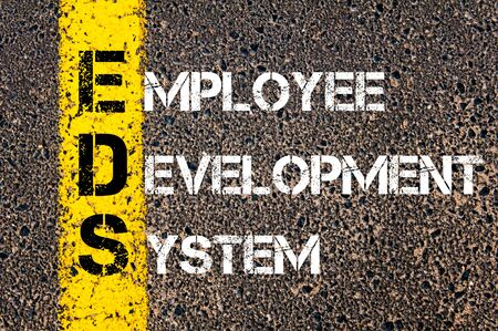 employee development: Concept image of Business Acronym EDS as Employee Development System  written over road marking yellow paint line.