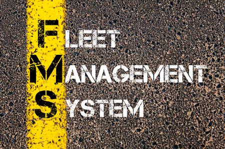 Concept beeld van bedrijf Acroniem FMS als Fleet Management System overschreven wegmarkering gele verf lijn. Stockfoto