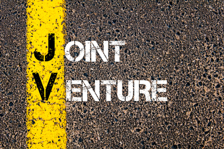 joint venture: Concept image of Business Acronym JV as Joint Venture  written over road marking yellow paint line.