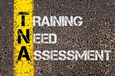 道路標示黄色塗装ライン上に書かれたトレーニング必要な評価としてビジネスの頭字語 TNA の概念イメージ。 写真素材