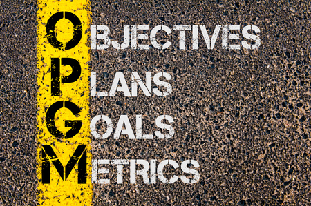 metrics: Concept image of Business Acronym OPGM as Objectives Plans Goals Metrics written over road marking yellow painted line.