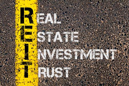 Concept beeld van bedrijf Acroniem REIT als Real Estate Investment Trust overschreven wegmarkering geel geschilderde lijn.