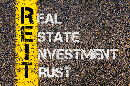 Concept image of Business Acronym REIT as Real Estate Investment Trust written over road marking yellow painted line.