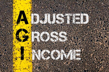 adjusted: Concept image of Business Acronym AGI as Adjusted Gross Income  written over road marking yellow paint line.
