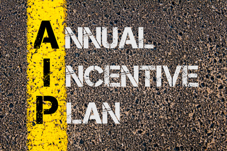 incentive: Concept image of Business Acronym AIP as Annual Incentive Plan  written over road marking yellow paint line. Stock Photo