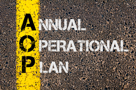 operational: Concept image of Business Acronym AOP as Annual Operational Plan  written over road marking yellow paint line. Stock Photo