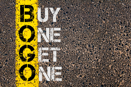 bogo: Concept image of Business Acronym BOGO as Buy One Get One  written over road marking yellow paint line.