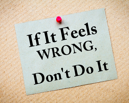 If It Feels Wrong, Dont Do It Message written on recycled paper note pinned on cork board Stock Photo