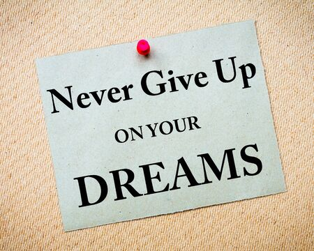 give up: Never Give Up On Your Dreams Message written on recycled paper note pinned on cork board Stock Photo