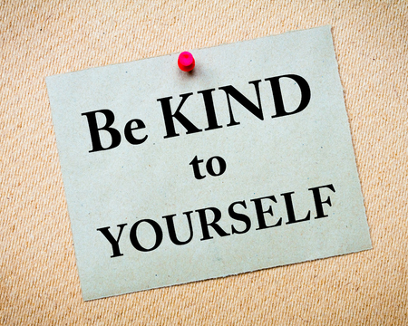 Be Kind To Yourself Message written on recycled paper note pinned on cork board
