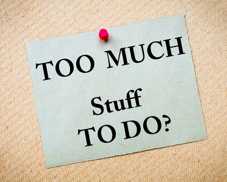 too: Too Much Stuff to Do Message written on recycled paper note pinned on cork board