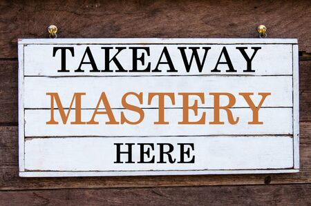 mastery: Takeaway Mastery Here Inspirational message written on vintage wooden board. Motivation concept image