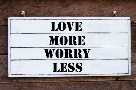 frame less: Love More Worry Less Inspirational message written on vintage wooden board. Motivation concept image