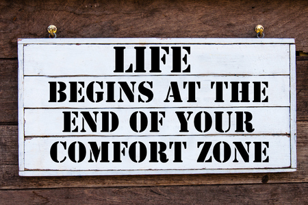 Life Begins At The End Of Your Comfort Zone Inspirational message written on vintage wooden board. Motivation concept image