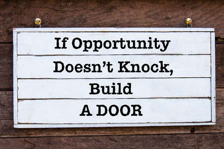 knock: If Opportunity Doesnt Knock, Build a Door Inspirational message written on vintage wooden board. Motivational concept image
