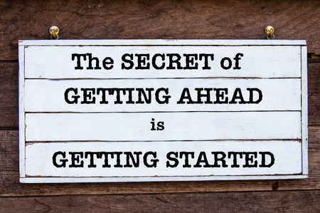 getting started: The Secret Of Getting Ahead Is Getting Started Inspirational message written on vintage wooden board. Motivational concept image Stock Photo