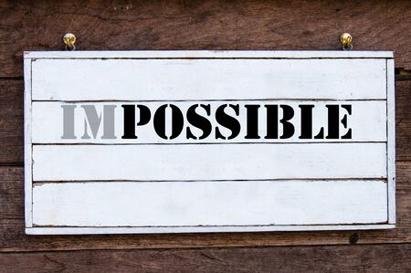 changed: Word Possible changed from Impossible, Inspirational message written on vintage wooden board. Motivational concept image