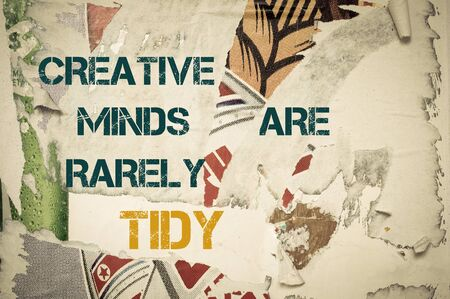 tidy: Creative Minds are rarely tidy- Inspirational message written on vintage grunge background with Old Torn Posters. Motivational concept image