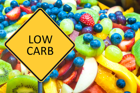 carb: Yellow roadsign with message LOW CARB over background of healthy fresh fruits Stock Photo