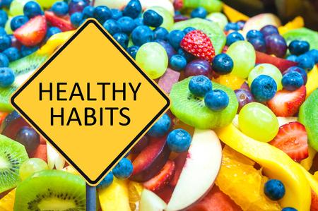habitos saludables: Letrero amarillo con mensaje HÁBITOS SALUDABLES sobre fondo de frutas frescas saludables Foto de archivo