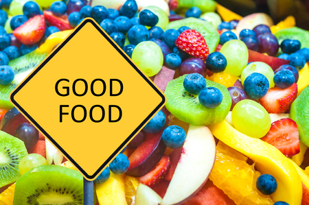 good food: Yellow roadsign with message GOOD FOOD over background of healthy fresh fruits Stock Photo