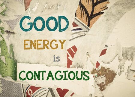 contagious: Good Energy is Contagious - Inspirational message written on vintage grunge background with Old Torn Posters. Motivational concept image