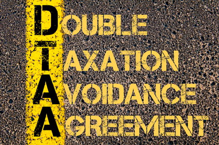 avoidance: Concept image of Business Acronym DTAA as DOUBLE TAXATION AVOIDANCE AGREEMENT written over road marking yellow paint line. Stock Photo