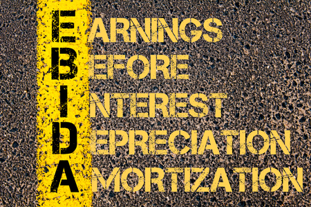 amortization: Concept image of Business Acronym EBIDA as EARNINGS BEFORE INTEREST DEPRECIATION AND AMORTIZATION written over road marking yellow paint line. Stock Photo