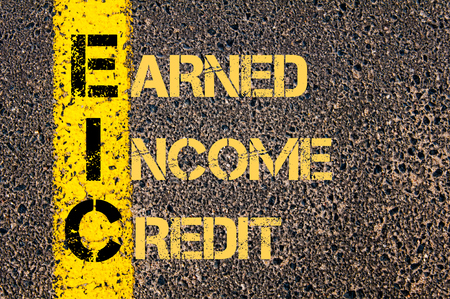 earned: Concept image of Business Acronym EIC as EARNED INCOME CREDIT written over road marking yellow paint line.