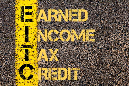 earned: Concept image of Business Acronym EITC as EARNED INCOME TAX CREDIT written over road marking yellow paint line. Stock Photo