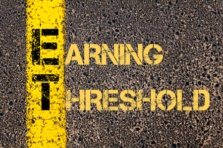 threshold: Concept image of Business Acronym ET as Earning Threshold written over road marking yellow paint line. Stock Photo