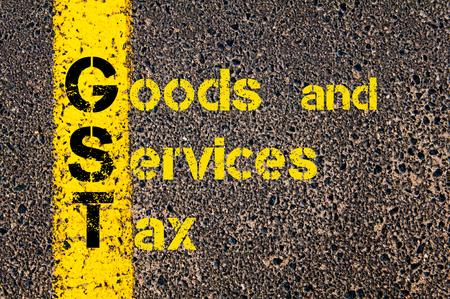 Concept beeld van bedrijf Acroniem GST als Goods and Services Tax overschrijven wegmarkering gele verf lijn.