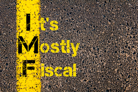 fiscal: Concept image of Business Acronym IMF as Its Mostly Fiscal written over road marking yellow paint line. Stock Photo