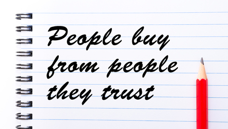 they: People Buy from People They Trust written on notebook page, red pencil on the right. Motivational Concept image