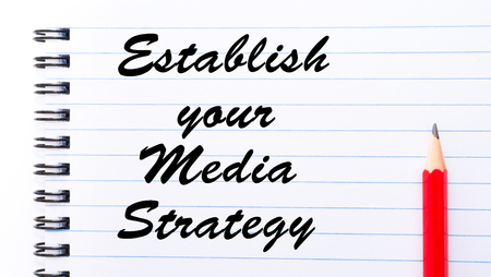 establish: Establish Your Media Strategy written on notebook page, red pencil on the right. Motivational Concept image