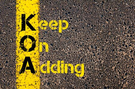 adding: Concept image of Business Acronym KOA as Keep On Adding written over road marking yellow paint line.