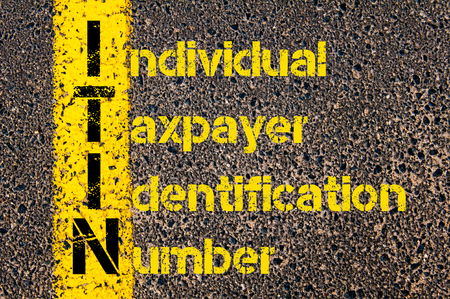 taxpayer: Concept image of Business Acronym ITIN as Individual Taxpayer Identification Number written over road marking yellow paint line.