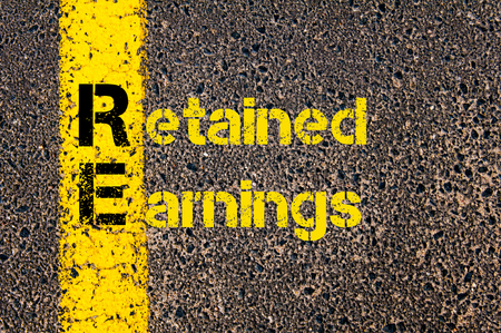 retained: Concept image of Accounting Business Acronym RE Retained Earnings written over road marking yellow paint line. Stock Photo