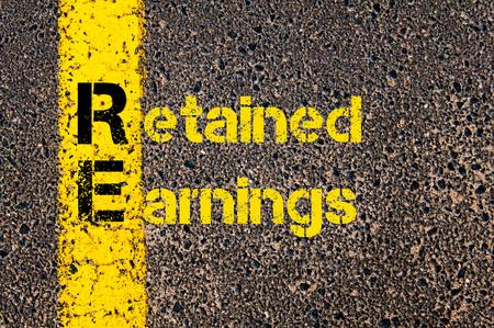 ganancias: Imagen del concepto de contabilidad de negocios acrónimo RE Ganancias retenidas por escrito sobre el marcado línea de pintura de color amarillo carretera. Foto de archivo