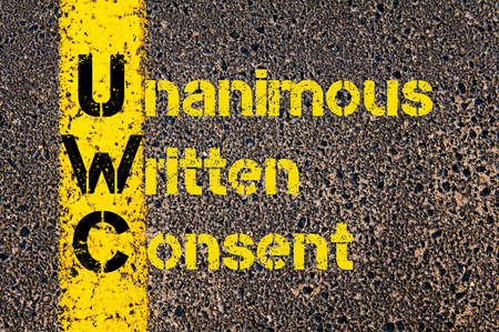 consent: Concept image of Accounting Business Acronym UWC Unanimous Written Consent written over road marking yellow paint line. Stock Photo