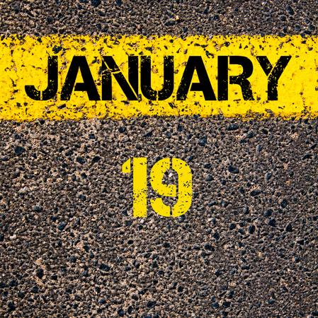19: 19 January calendar day written over road marking yellow paint line