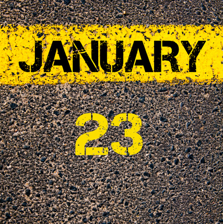 road marking: 23 January calendar day written over road marking yellow paint line Stock Photo