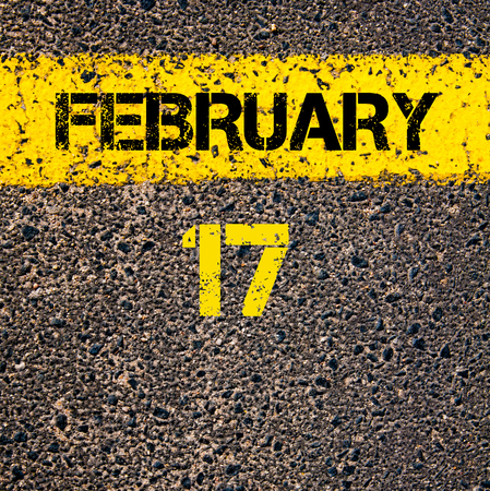 road marking: 17 February calendar day written over road marking yellow paint line