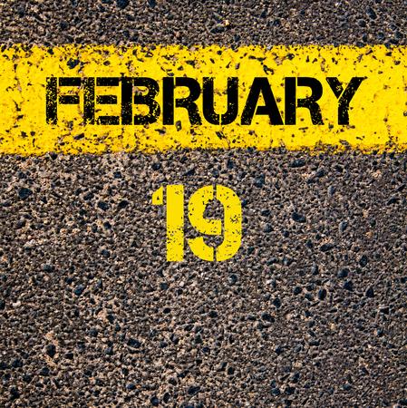 19: 19 February calendar day written over road marking yellow paint line