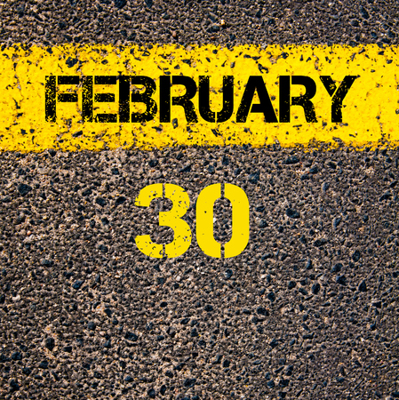 road marking: 30 February calendar day written over road marking yellow paint line Stock Photo